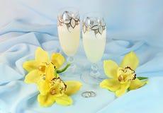 Orchideeën, champagne en trouwringen Stock Foto's