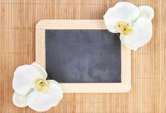 Orchideeën met bord op bamboeachtergrond stock fotografie