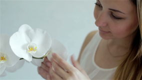 Orchidee bianche odoranti della bella giovane donna e toccare i petali con le sue dita video d archivio