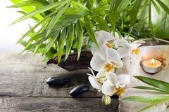 Orchidee candle i kamienie na drewnianych deskach Obrazy Stock