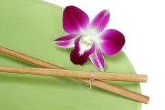 Orchidee-Ess-Stäbchen und Platte Stockbild