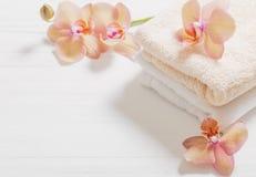 Orchidee met handdoeken op witte houten achtergrond royalty-vrije stock afbeeldingen