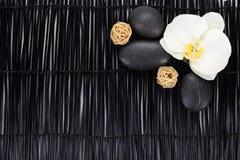 Orchidee met zenstenen en rieten ballen op zwarte achtergrond royalty-vrije stock fotografie