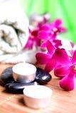 Orchidee und Kerzen mit Tüchern und Kieseln Lizenzfreies Stockfoto