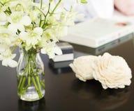 Orchideen im Vase auf hübschem Nachttisch quadrieren stockfotos