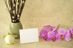 Orchids and blank card. Lotus flower bulbs on handmade paper with blank card for text and orchid flowers for holiday or spa invitation Royalty Free Stock Photography