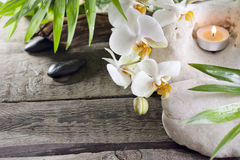 Orchids candle and stones on wooden boards Royalty Free Stock Photography