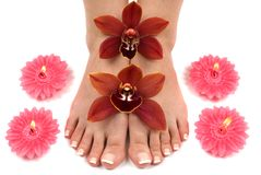 Orchids and Feet. Feet with beautiful fresh orchids and candles Stock Photo
