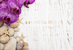 Orchids and massage stones. On a wooden background Stock Photos