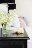 Orchids in vase on pretty bedside table vertical Stock Images