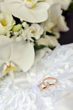 Orchids and wedding rings Stock Photography