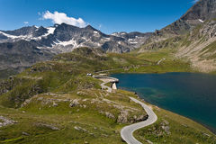 Orco valley - Agnel lake and road over dam. The road to nivolet pass curves over the dam Royalty Free Stock Photography