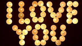 Ord ÄLSKAR JAG DIG som bildas av glödande stearinljus och dekoreras med blommor