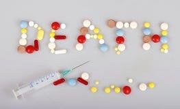 Ord av död, minnestavlor, preventivpillerar, kapslar och injektionssprutan Arkivfoton