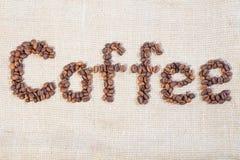 Ord av kaffebönor som ut läggas Arkivfoto