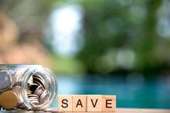 Ord av sparande pengarbegrepp samlade i korsord med träkuber Mynt mycket av glass piggy Royaltyfria Bilder