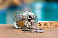 Ord av sparande pengarbegrepp samlade i korsord med träkuber Mynta mycket av den glass piggy valda fokusen Royaltyfri Bild