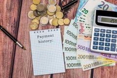 Ord för betalninghistoria i notepaden med euro, räknemaskin, mynt Arkivbilder
