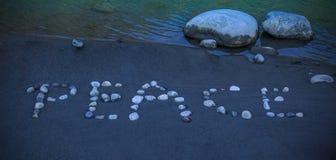 Ord för `-fred` som är skriftligt med kiselstenar på sanden Royaltyfri Foto