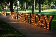 Ord för LYCKLIG FÖDELSEDAG med glödande ljusa kulor Arkivfoton