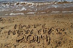 Ord för lyckligt nytt år som 2014 är skriftliga i sand Arkivfoto