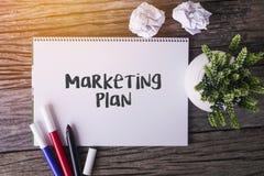Ord för marknadsföringsplan med notepaden och den gröna växten på träbackg Royaltyfri Fotografi