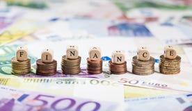 Ord Financen på myntbuntar, kontant bakgrund Royaltyfri Foto