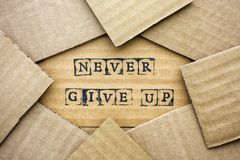 Ord Give Up gör aldrig vid svarta alfabetstämplar på papp royaltyfri bild