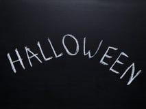 Ord halloween som är handskriven på den svart tavlan Royaltyfri Foto