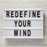 Ord 'omdefinera för din mening 'på modernt bräde över vit träbakgrund, bästa sikt Över huvudet plant lägga arkivbild