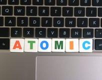 Ord som är atom- på tangentbordbakgrund Royaltyfria Bilder