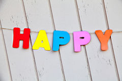 Ord som är lyckligt vid kulöra bokstäver på staketet Arkivfoton