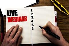 Ord som skriver Live Webinar Affärsidé för E-att lära för affärsrengöringsduk som är skriftligt på boken, träbakgrund med affärsm royaltyfri fotografi