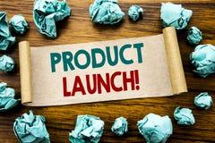 Ord som skriver produktlanseringen Affärsidéen för nya produkter startar skriftligt på klibbigt anmärkningspapper, träbakgrund me royaltyfri bild