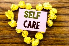 Ord som skriver självomsorg Affärsidé för att ta att att bry sig för egen hälsa som är skriftlig på klibbigt anmärkningspapper på Arkivfoto