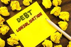 Ord som skriver skuldbefästning Affärsidé för pengarlånkreditering som är skriftlig på klibbigt anmärkningspapper, träbakgrund me royaltyfri bild