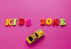 Ord`-ungar zonplanerar ` med leksakbilar på rosa bakgrund Arkivfoton