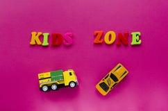 Ord`-ungar zonplanerar ` med leksakbilar på rosa bakgrund Royaltyfri Foto