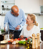 Ordatary mature couple cooking Spaniard tomatoes Royalty Free Stock Photography