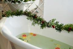 Ordeñe el agua en el baño, que nadan la fruta cítrica: cal, limón y pomelo El cuidado de piel y el baño de la relajación llenaron fotos de archivo