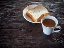 Ordeñe el café en las hojas blancas del pan de la taza y del trigo integral de la porcelana Foto de archivo