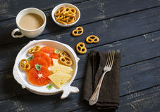 Ordeñe el té, las naranjas, el queso y las galletas en una placa blanca en una superficie de madera oscura Foto de archivo