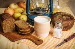 Ordeñe en loza de barro, pan de centeno, sal y sal, las verduras y linterna de keroseno en una tabla de madera Imagenes de archivo