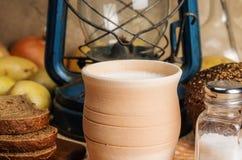 Ordeñe en mercancías de cerámica, pan de centeno, coctelera de sal con la sal, verduras y linterna de keroseno en una tabla de ma Foto de archivo libre de regalías