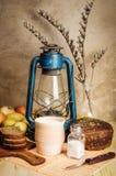 Ordeñe en un pote de cerámica, pan de centeno, tabla de cortar, coctelera de sal con la sal, la cebolla, la patata, el cuchillo,  Fotos de archivo