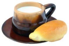 Ordeñe en una taza de cerámica y una empanada en blanco. Imagenes de archivo