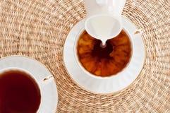 Ordeñe la colada en la taza de té Fotografía de archivo libre de regalías