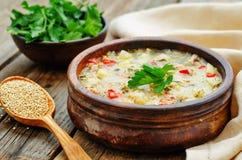 Ordeñe la sopa con las patatas, la quinoa y pimientas Foto de archivo
