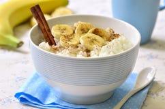 Ordeñe las gachas de avena del arroz con el plátano, el canela y la miel imagen de archivo libre de regalías