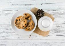 Ordeñe, las galletas en una tabla de madera texturizada blanco Imagen de archivo